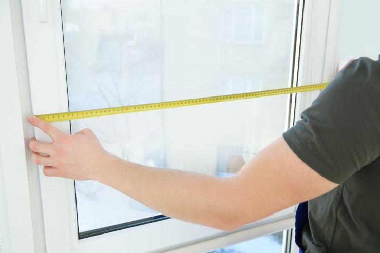 La miroiterie garrido réalise des projets de menuiseries qui se passent bien : ici, l'artisan métreur mesure l'encadrement d'une fenêtre avant de l'installer